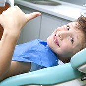 Smiling little boy in dental chair giving thumbs up