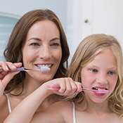 Mother showing daughter how to brush teeth