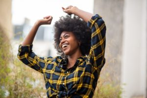 Woman with full set of teeth smiling outside enthusiastically