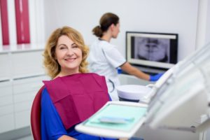 Older woman smiling while sitting in the dental chair during a consultation